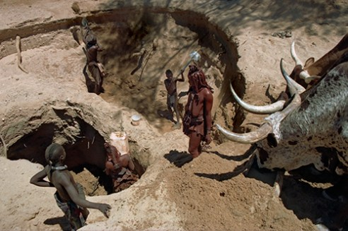 Nuku's children haul water from a three-tiered hand dug waterhole and keep the walls of the tidy in order to prevent them from caving in. Etanga, Kunene North Region, Namibia, 2000