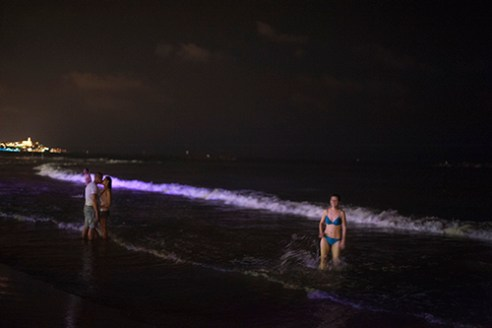 Young swiming at night on the beaches of Tel Aviv.