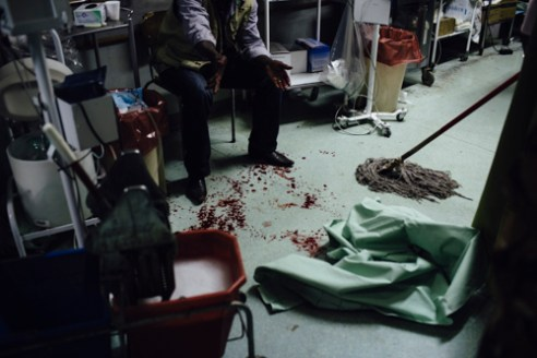 The cleaner of the casualty ward swipes blood from the floor of the inspection area. Namibia suffers an ongoing lack of medical professionals.