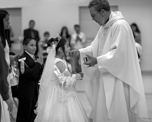 Catholic priest celebrates first communion with young girl in an Hispanic Catholic church in Charlotte, NC.
