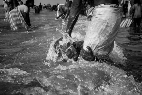An old woman hangs on to her husbands legs as the man hold her down to take a dip in the cold water during winter during a religious event.