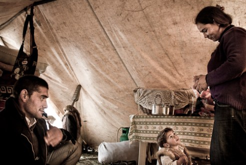 Inside the tent where he lives with his wife and child. No doors, no bathroom.