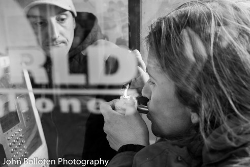 A young woman smokes crack cocaine in a city centre public telephone box, watched by her partner. Sights like this are not uncommon but are largely unnoticed by the general public.