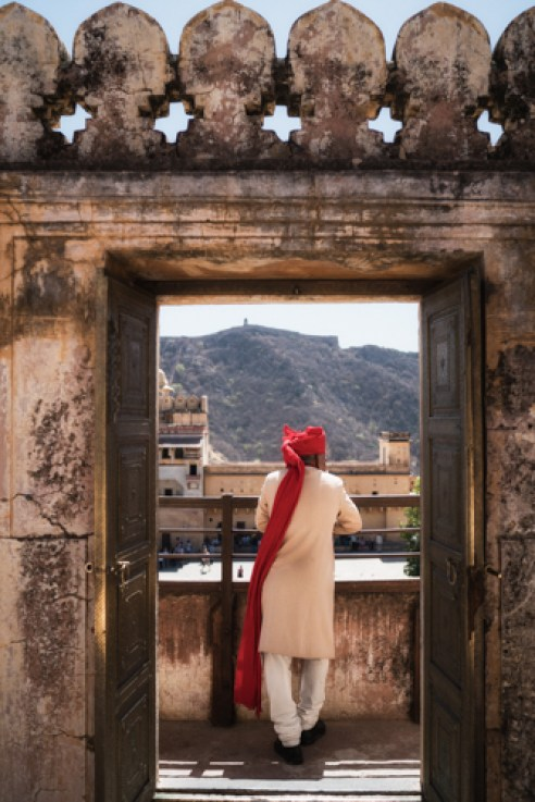 Amer Fort, Jaipur. The fort, built in the hills in the 1600's, looks down over Jaipur. A local tourist looks down into the fort.