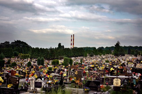 A modern cemetery in the town of Oswiecim with smokestacks from the town's chemical factory looming in the distance. The factory was built by Nazi Germany during the war and used prisoners from Auschwitz to run it. After the war the new communist government expanded the industrial complex, which employed about 12,000 employees. After the fall of communism in Poland the factory became privatized and now only employs about 1,500 people.