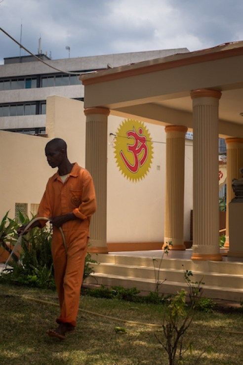 A man waters the garden at the city of Blantrye's Shree Hindu temple. Indians originally arrived in Malawi as labourers for building railways, and comprise a small minority of the Malawian population today.