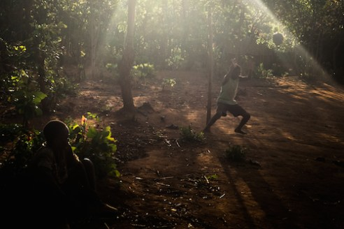 A goalkeeper leaps to defend a soccer ball in on a pitch amongst a forest outside Livingstonia. The town was founded in 1894 by Scottish missionaries, who chose the location in the highlands to avoid malaria-carrying mosquitoes along the lake.