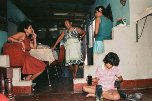 Angela's daughter, Anna polishes shoes with black paint while her mother and grandmother talk.