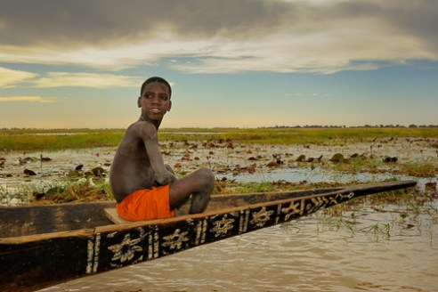 Little Fulani boy in handmade canoe. Near Djenne