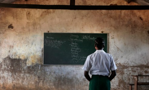 Young girl reads there words on a classroom chalkboard while learning English at a school near Xia-Xia, Mozambique. (2005)