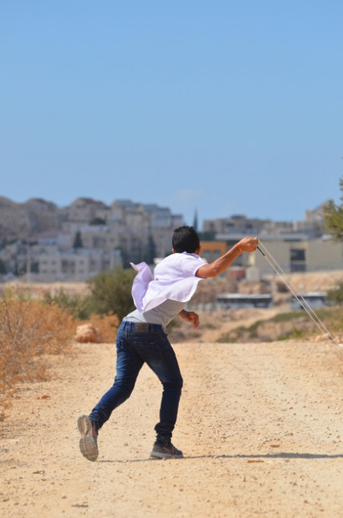 "Bil'in Stone throw: A young man throws a rock using a slingshot in the village of Bil'in West Bank. Some young men show their opposition to the ""Israeli occupation of Palestinian land"" by pelting the Israeli forces with stones."
