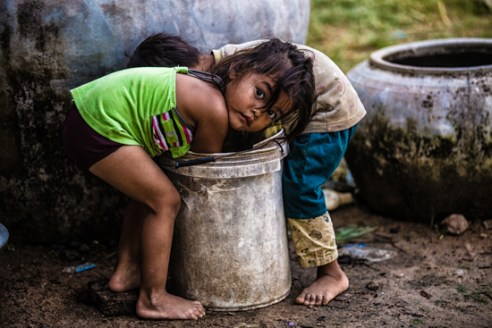 A young girl washes her hands after helping her mother make clay pots to sell at the local market Rural Cambodia