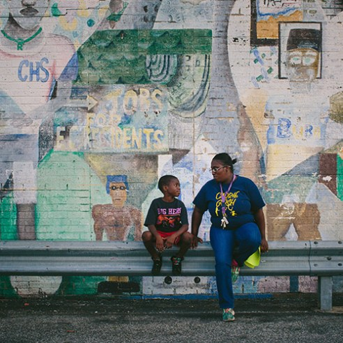 """East Chicago, Indiana Nayesa Walker and her 7-year-old son Kash Lott wait for a school bus to drop off his two younger siblings at the West Calumet Housing Complex. As a child, Walker helped create the mural that covers the neighborhood's community center. Walker and other residents tried to stop the neighborhood's demolition. """"We feel like we're just being thrown out,"""" Walker said."""