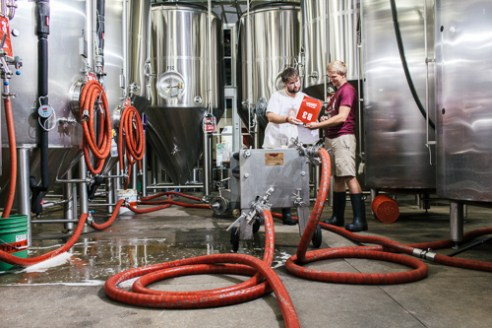 Durham, North Carolina - Wednesday July 7, 2016 - Cody Welch, left, and Charlie Ewing look over brew sheets during beer production in the Fullsteam Brewery in Durham, North Carolina.