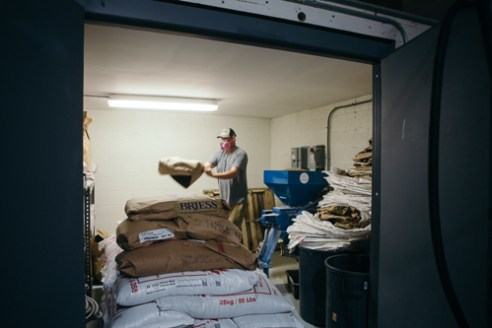Durham, North Carolina - Wednesday July 7, 2016 - Eric Lebsack loads bags of grain into a conveyor while preparing to brew a batch of the Ponysaurus Rye Pale Ale Wednesday morning at the brewery in Durham, North Carolina.