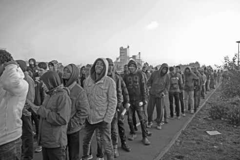 Calais line up Refugees queue outside the processing centre before boarding buses. Many people decided not to take the offer of asylum in France and plan to continue their journey to the UK.