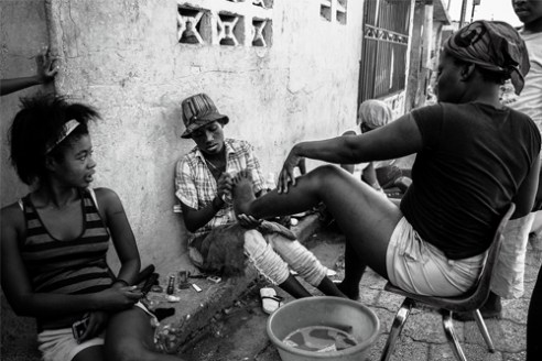 Women pedicure their feet on one of the main roads of their quarter inside the mega-slum