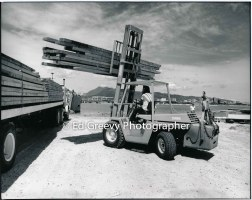 A forklift unloads donated lumber on Mokauea Island for new homes. 4053-4-19A 4-20-79