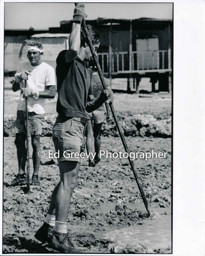 John Kelly looks on as Jon Olson works on the Mokauea Island fishpond construction. 5001-2-26A 4-13-80