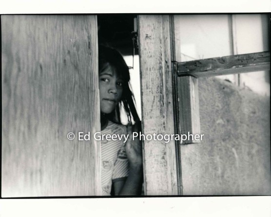 Young Mokauea Island girl peeks out from her front door. 2914-8-9A 8-26-75