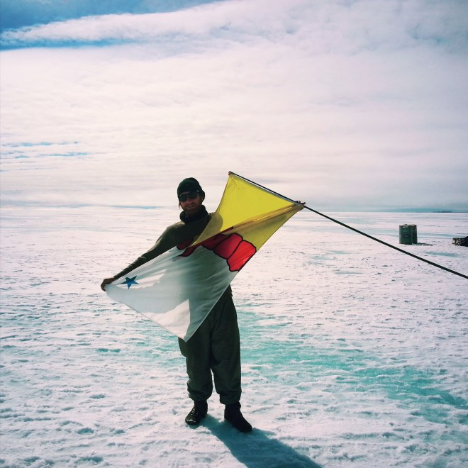 Holding the Nunavut flag at camp