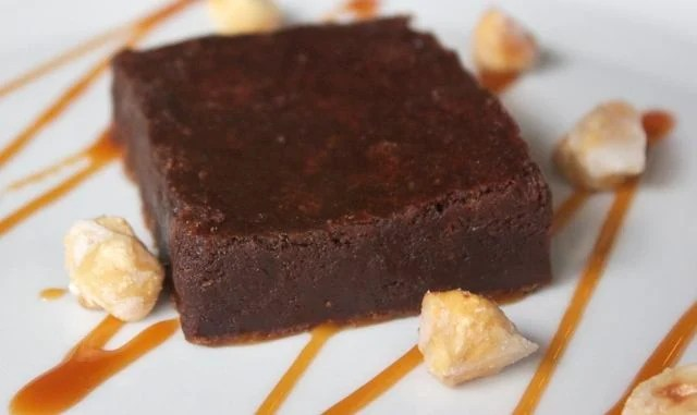 Nutella brownie on plate with caramel sauce and hazelnuts
