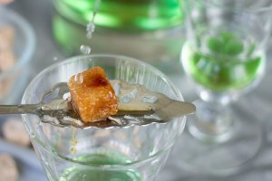Drizzling water on sugar cube over absinthe cocktail
