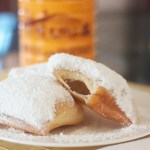 Beignets dusted with sugar on plate.