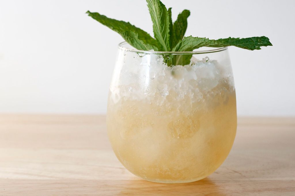Mint julep garnished with fresh mint in stemless wine glass on wood.