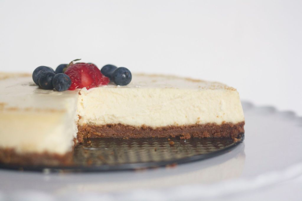 Mascarpone cheesecake with a graham cracker base, garnished with fresh berries on a cake plate.