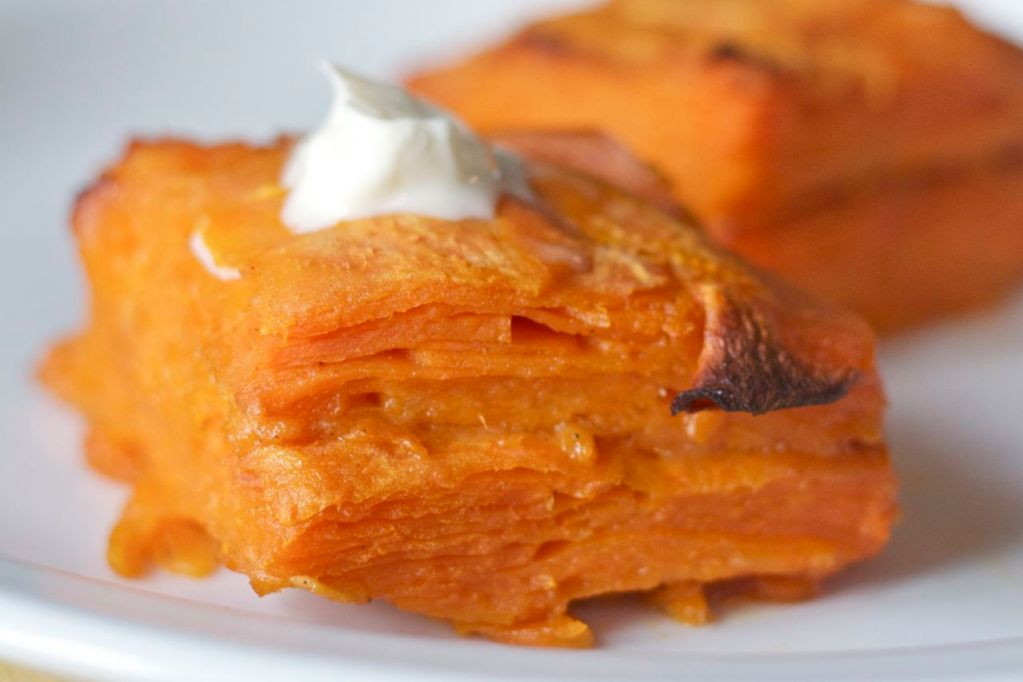 Baked sweet potato gratin on plate with creme fraiche on top.