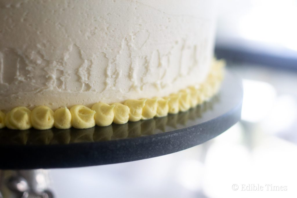Yellow dots piped around bottom of round layer cake.