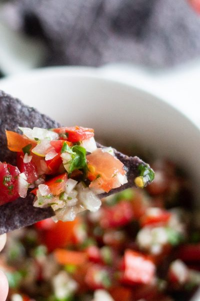 Pico de gallo on a blue corn tortilla chip.