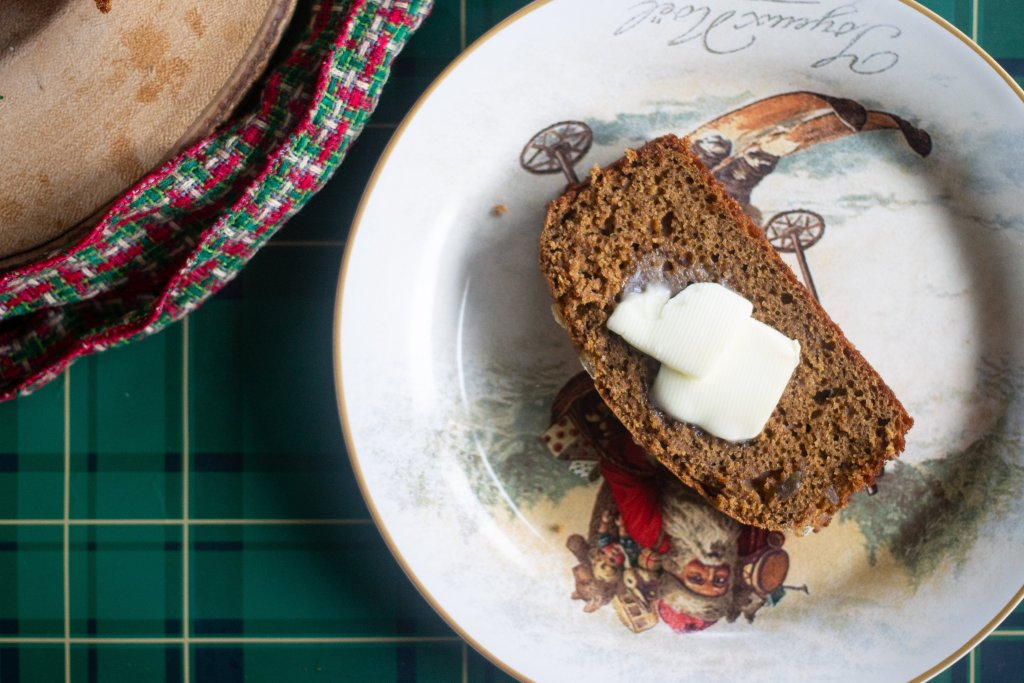 Slice of gingerbread on Christmas plate with butter on top.