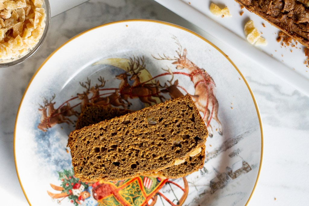 Gluten-free gingerbread loaf slices on Christmas plate with candied ginger on the side.