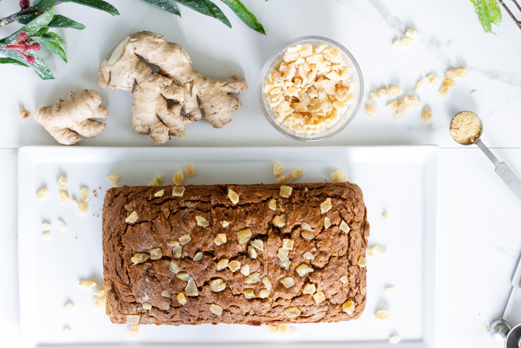 Whole gingerbread loaf on rectangle plate with fresh ginger root and crystallized ginger.