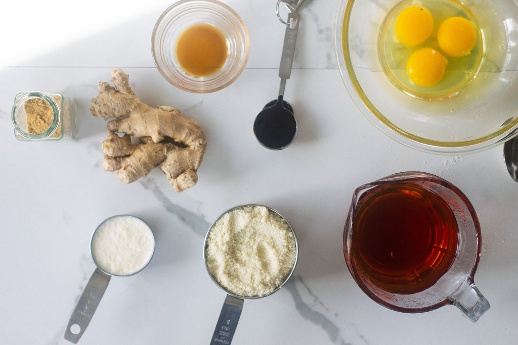 Ingredients for gluten-free treacle tart on counter: eggs, molasses, treacle syrup, almond flour, cream, ginger and vanilla.
