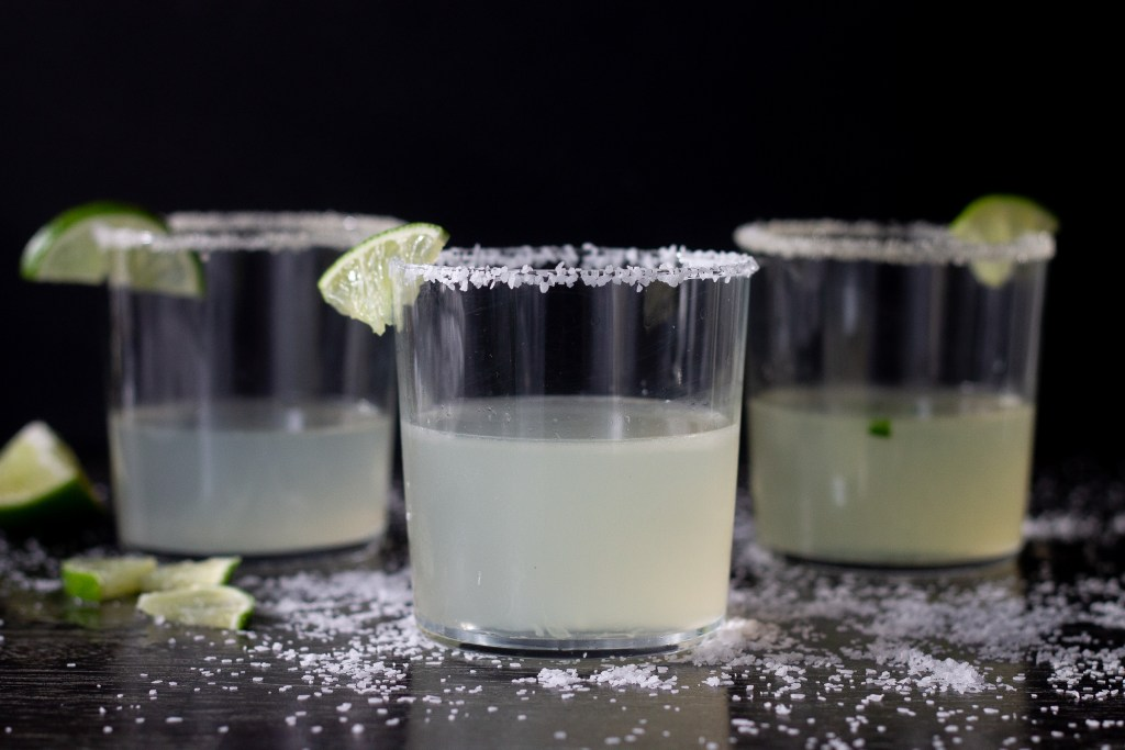 Three margaritas on a counter covered with salt.