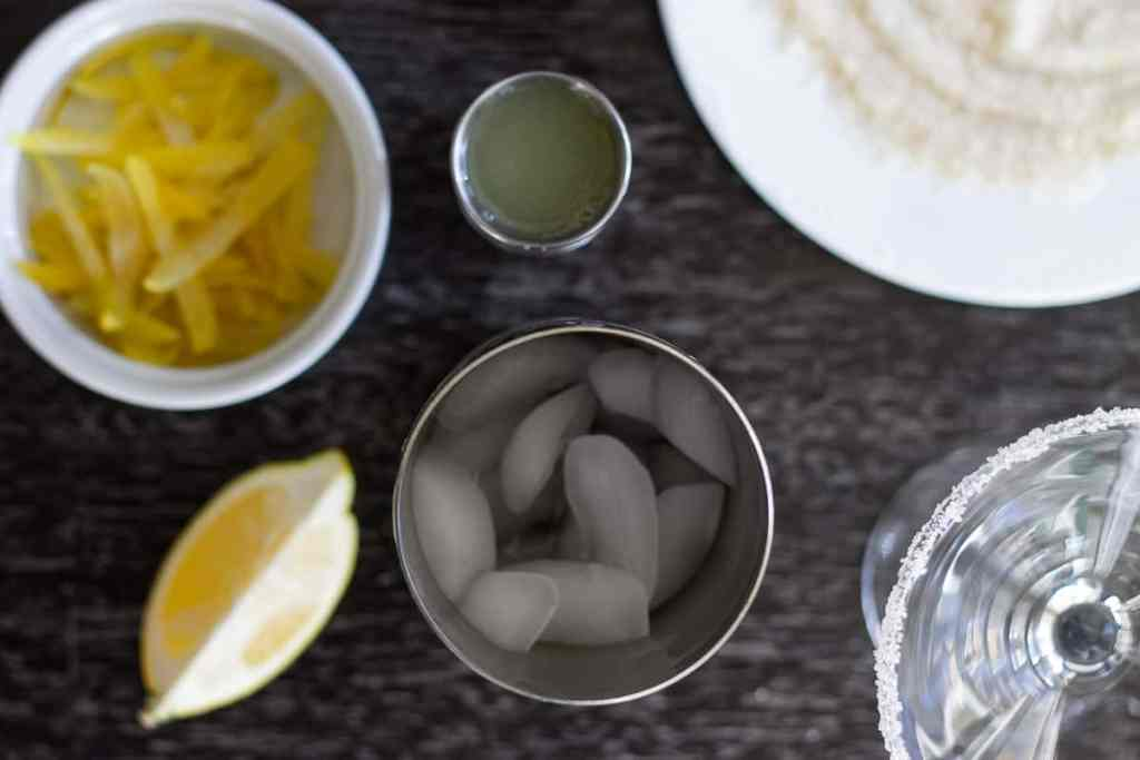 Ingredients for lemon drop cocktail, with cocktail shaker with ice.