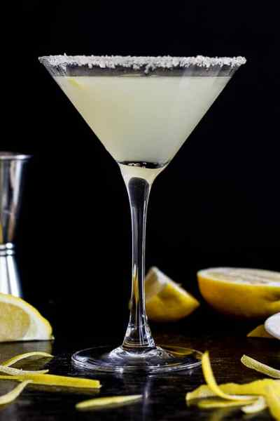 Looking down on lemon drop cocktail, next to lemon peel strips.