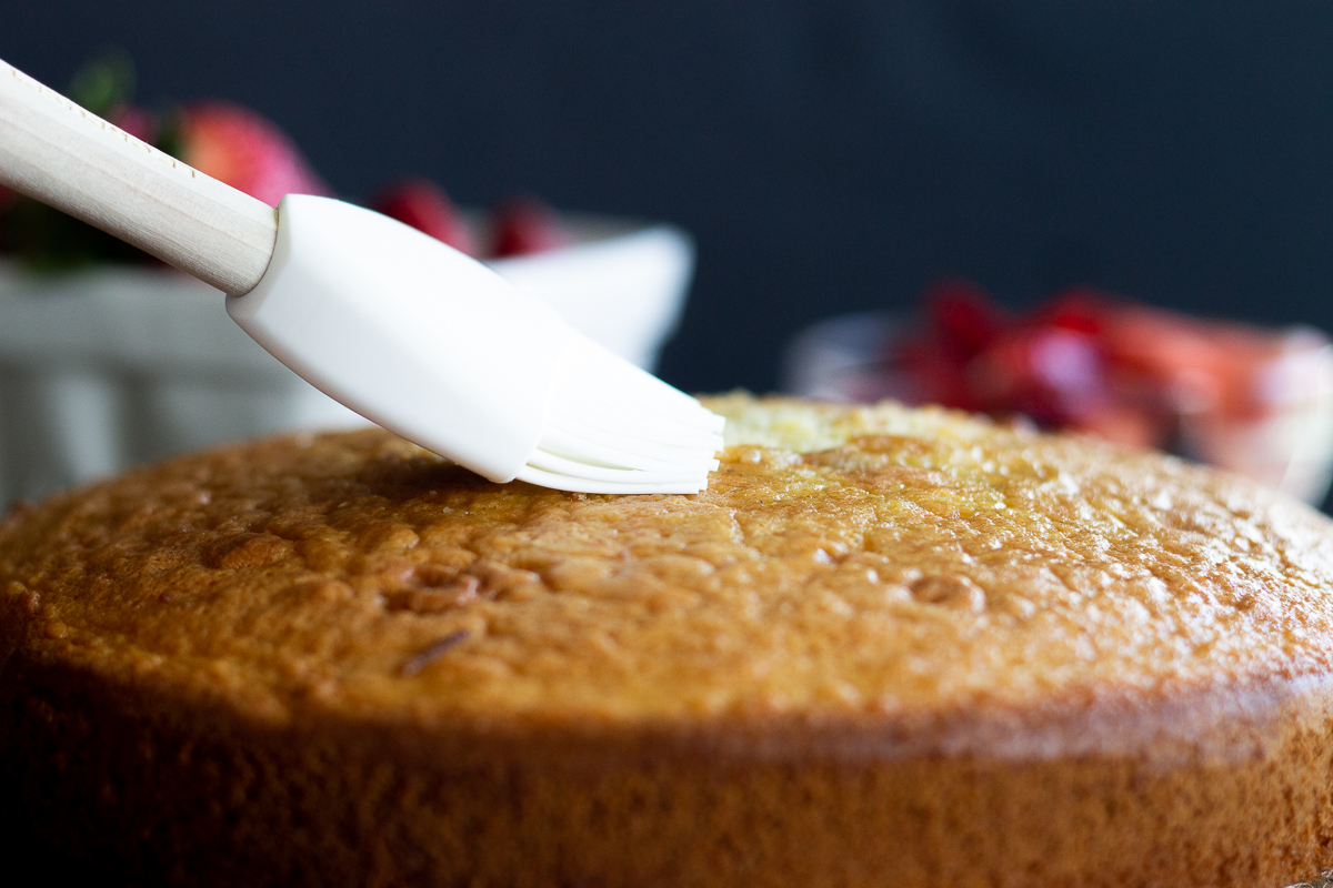 Pastry brush on top of gluten free vanilla cake, brushing in liqueur.