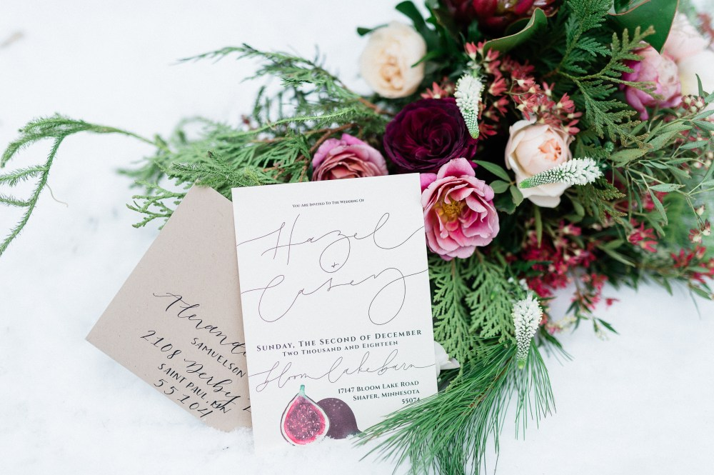 Wedding invitation and florals with evergreens.