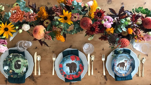 Fall flowers in a running centerpiece on a wooden table with Anthropologie plates painted with woodland creatures