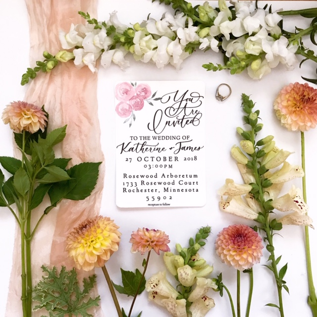 Flatlay image of wedding invitation with peach and white flowers and blush-colored silk ribbon.