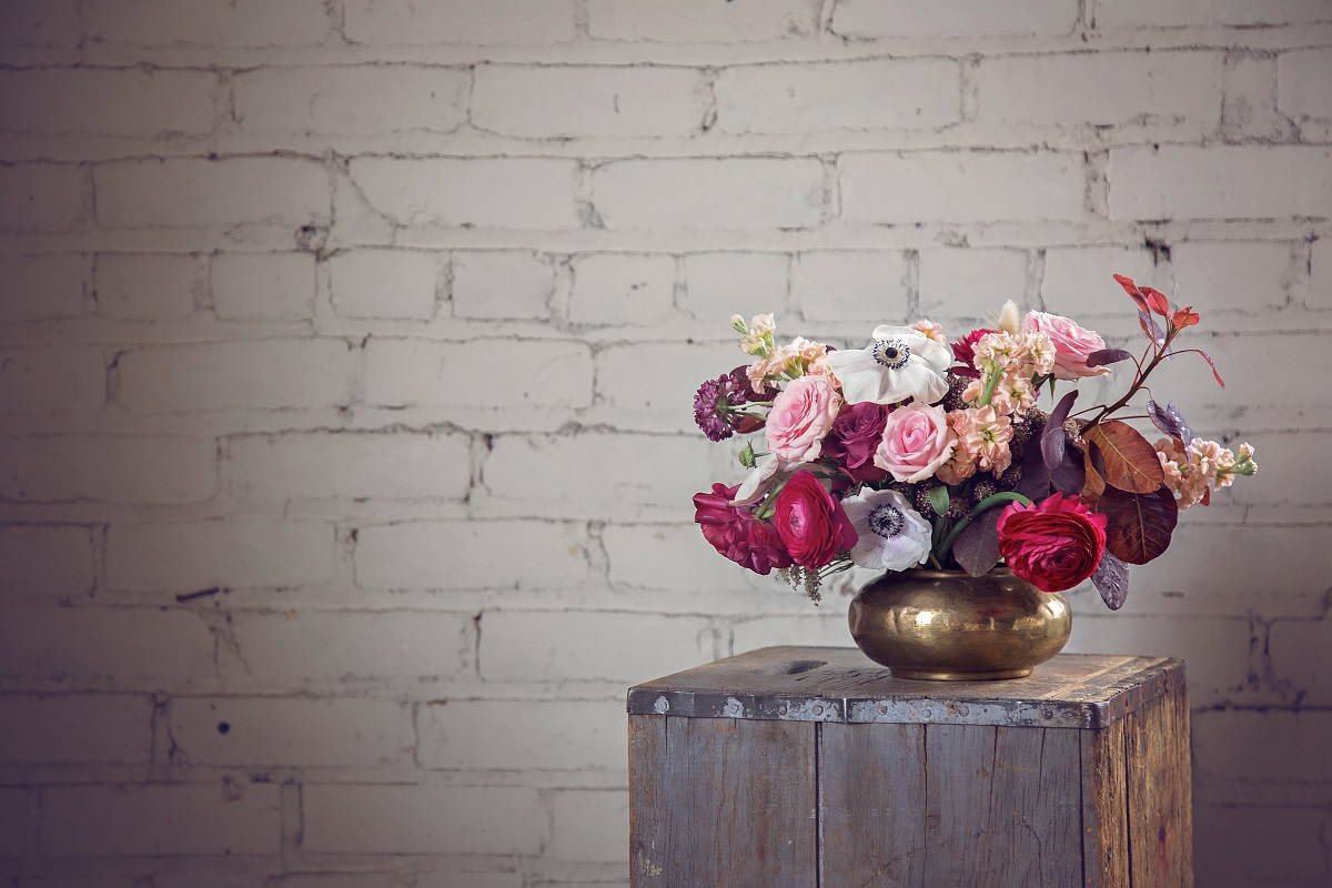 Flower arrangement of ranunculous, anemones, roses and smokebush on a wooden pedestal in front of a white brick wall.