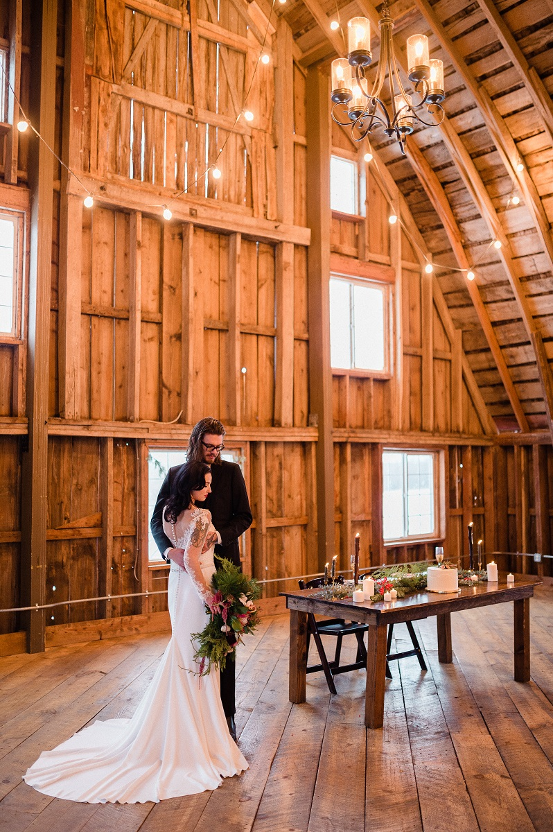 Bride and groom standing in a well-lit barn with high ceilings.