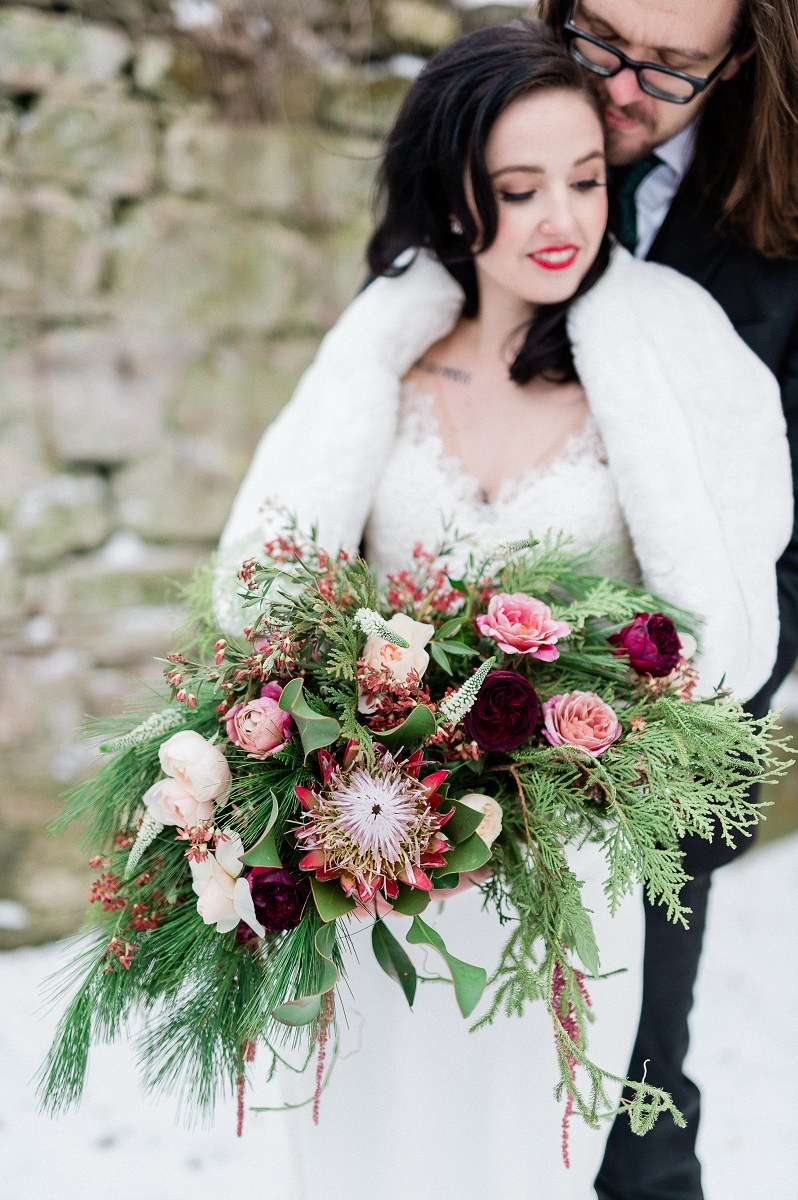Light-skinned woman in a fur shawl and wedding gown with bouquet of winter evergreens, roses and king protea. Groom is hugging her.