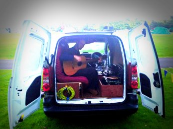 A performer practising in his van