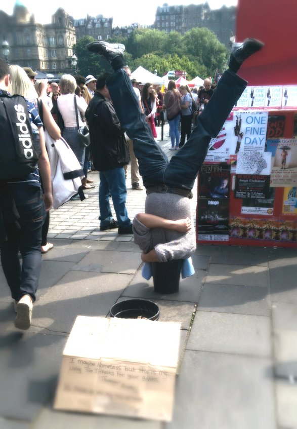 Street Performer at Edinburgh Fringe with head in bucket