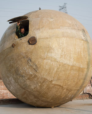 """Farmer Liu Qiyuan looking out from a survival pod that he built and also dubbed """"Noah's Arc"""". (Ed Jones, AFP)"""
